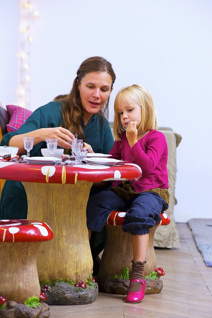 Mother with small daughter at laid table