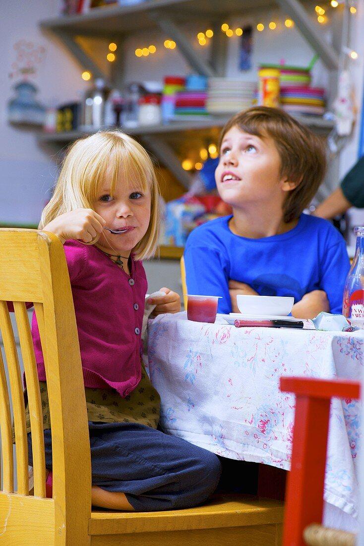 Children eating breakfast in kitchen