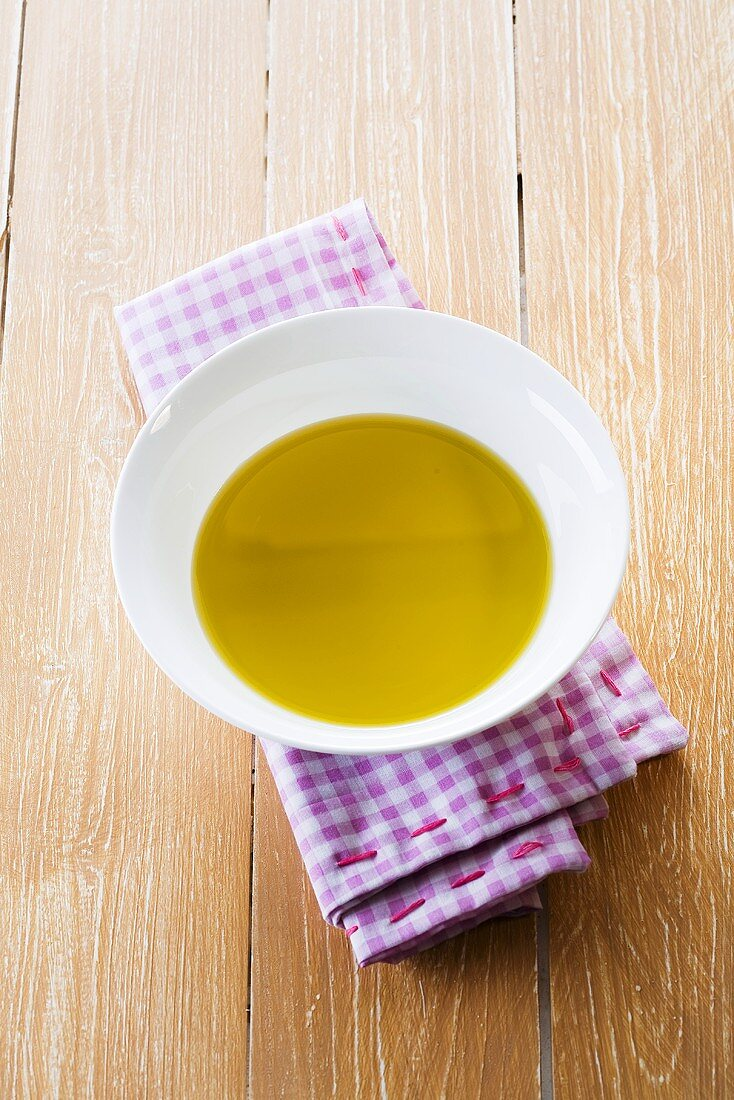 Olive oil in small dish on checked cloth