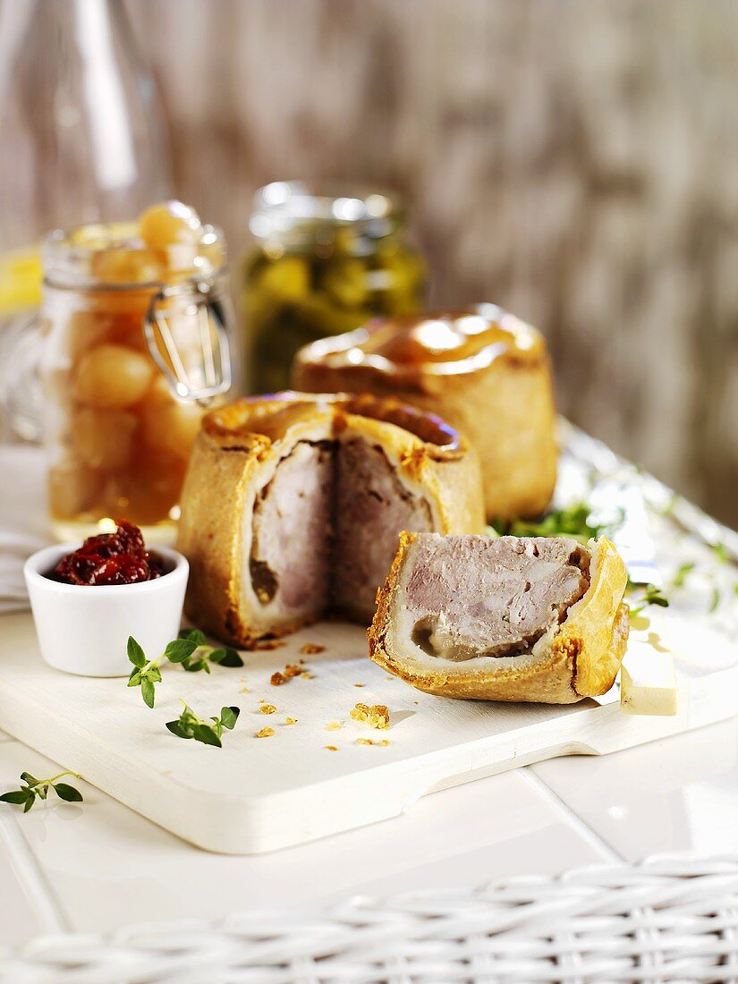 Pork pies (one with a piece cut), pickled onions & gherkins