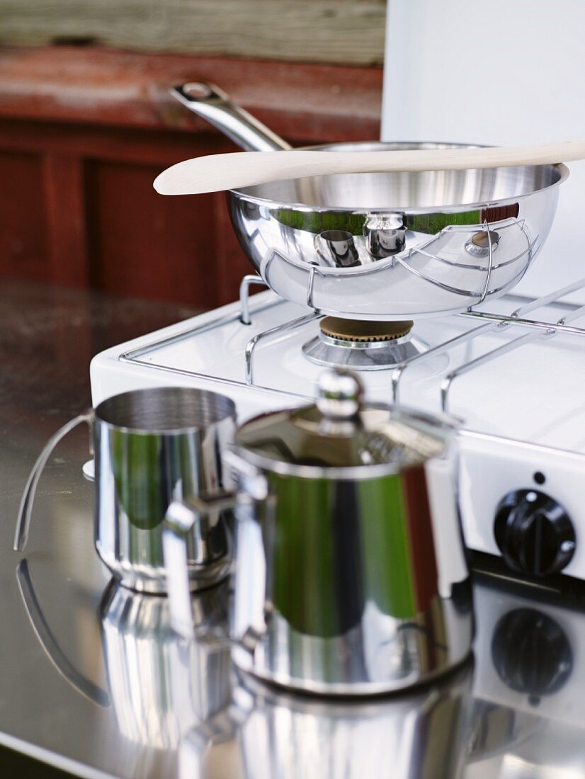 Frying pan on gas cooker and stainless steel tableware