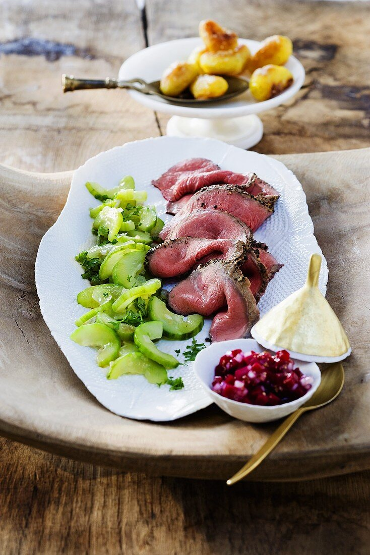Slices of roast beef with cucumber salad, salsa and potatoes