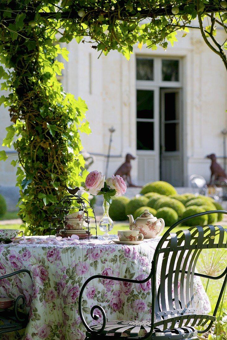 Romantic tea table in garden, Château de la Verrerie, France