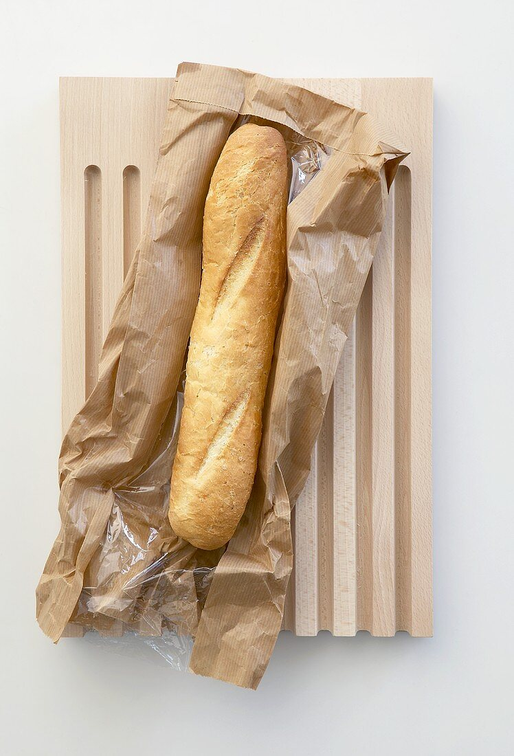 Baguette with paper bag on breadboard