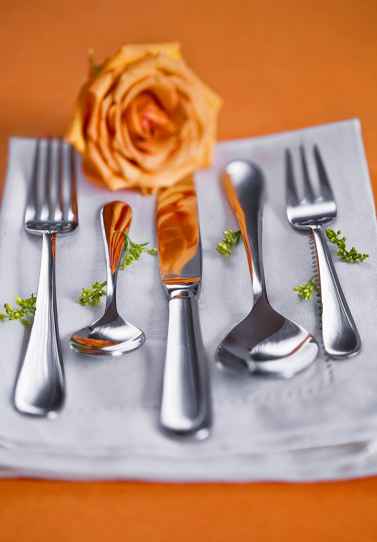 Cutlery on napkin with orange rose