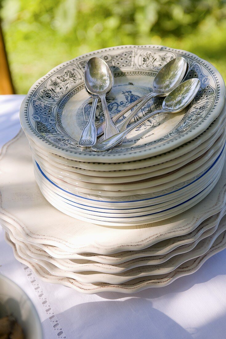 Stack of plates with spoons on table in garden