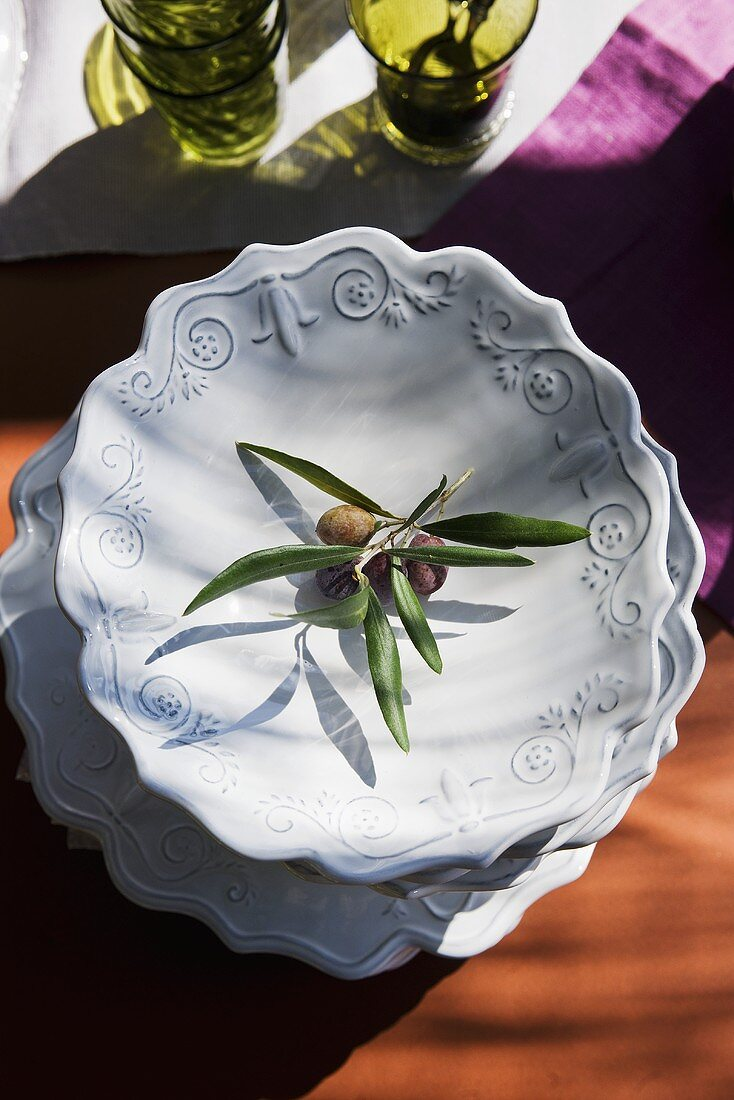 Pile of plates with olive sprig