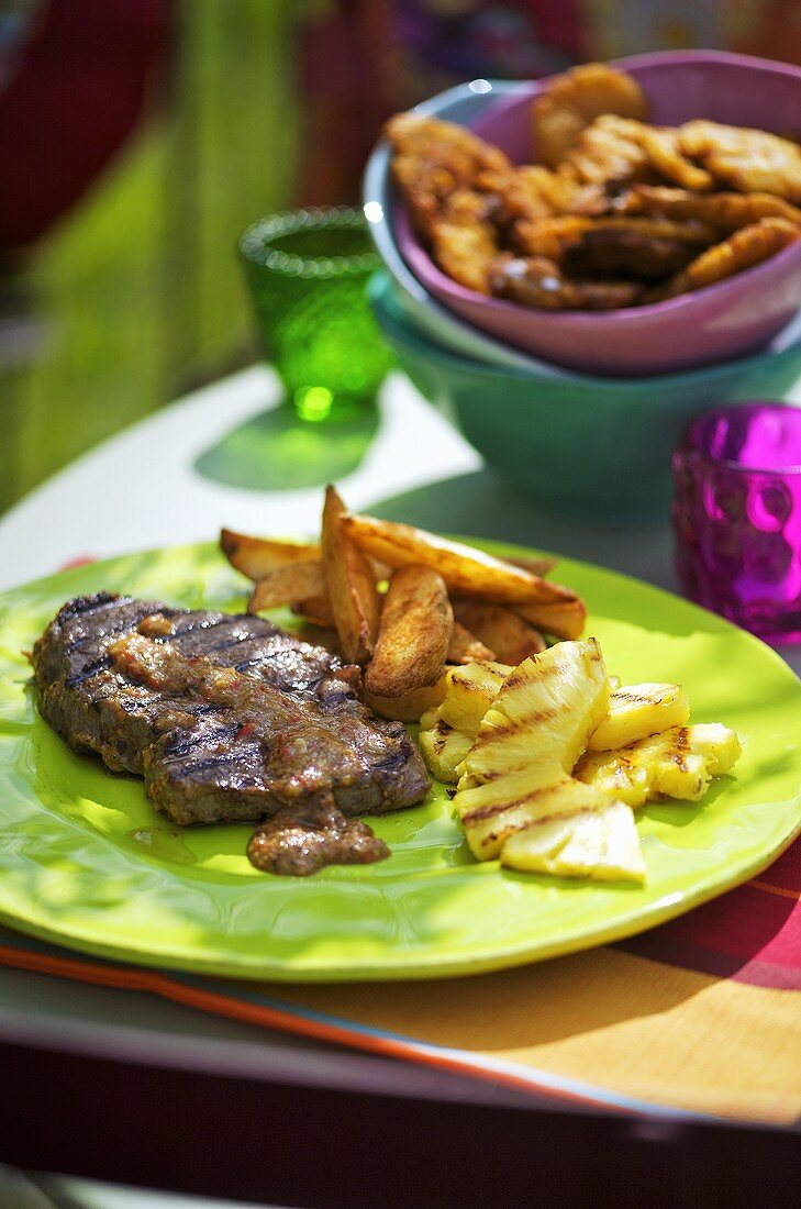Jamaican steaks with potato wedges and pineapple