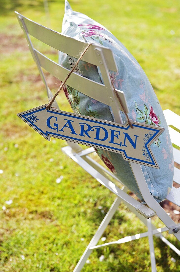 Chair with cushions and signpost to garden