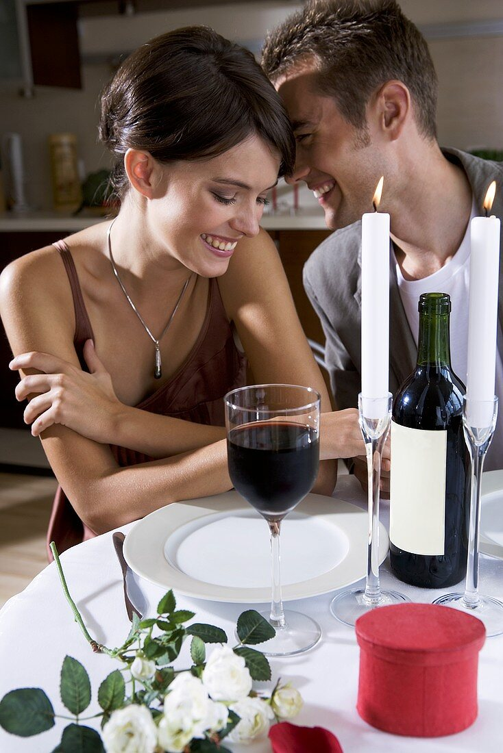 Young couple with red wine by candlelight