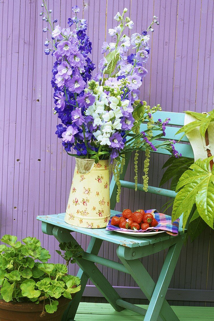 Garden chair with delphiniums and plate of strawberries