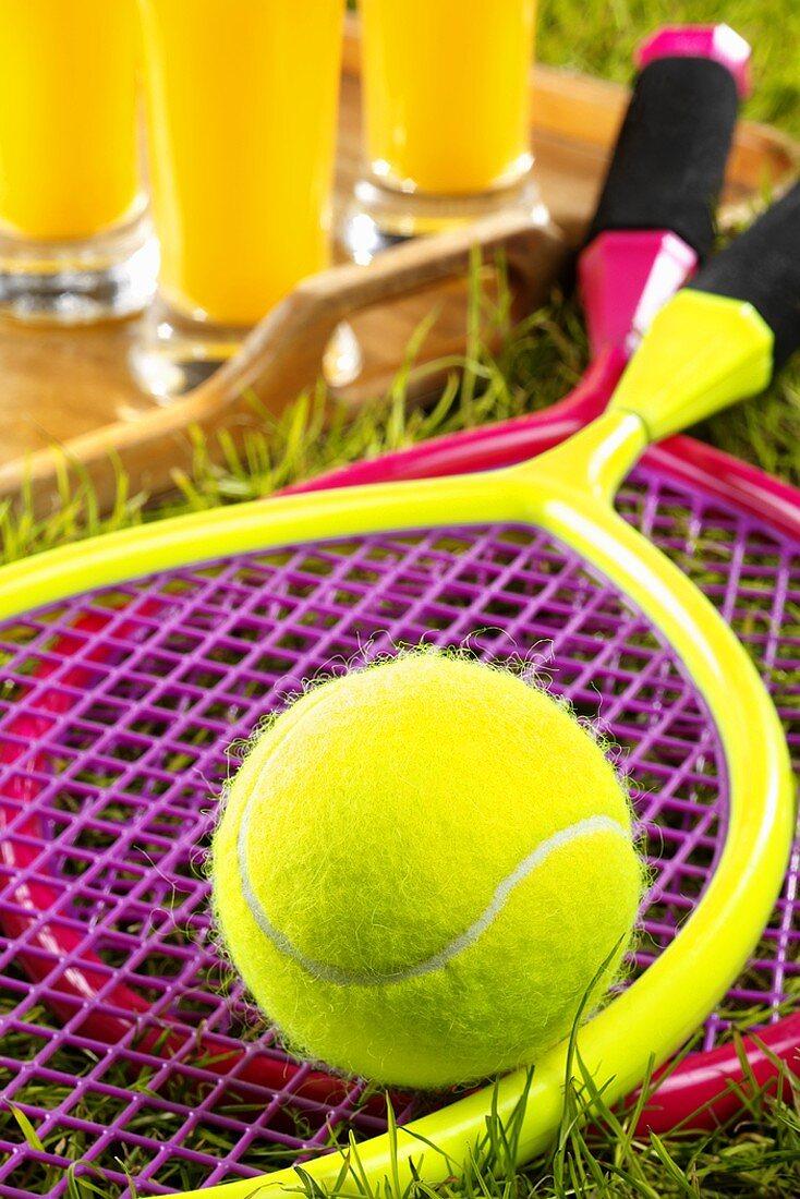 Children's tennis rackets & ball in grass, orange juice behind