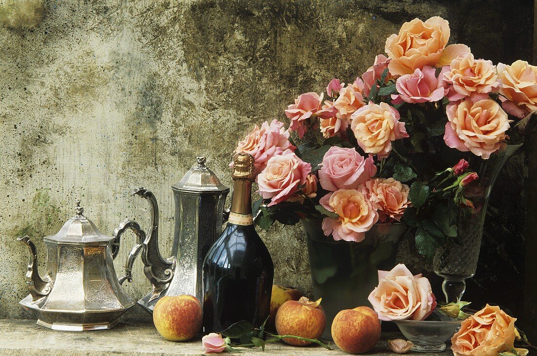 Silver coffee pot and teapot, champagne and vases of roses