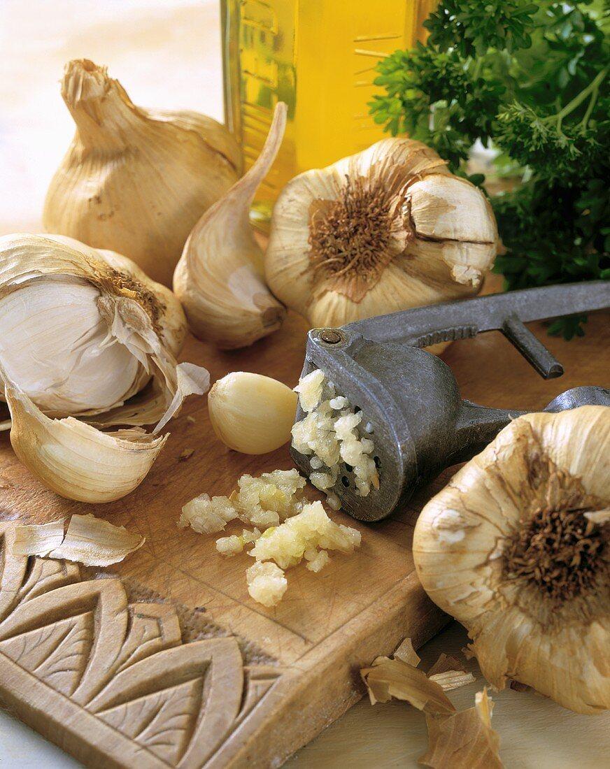 Garlic, garlic press, olive oil and parsley