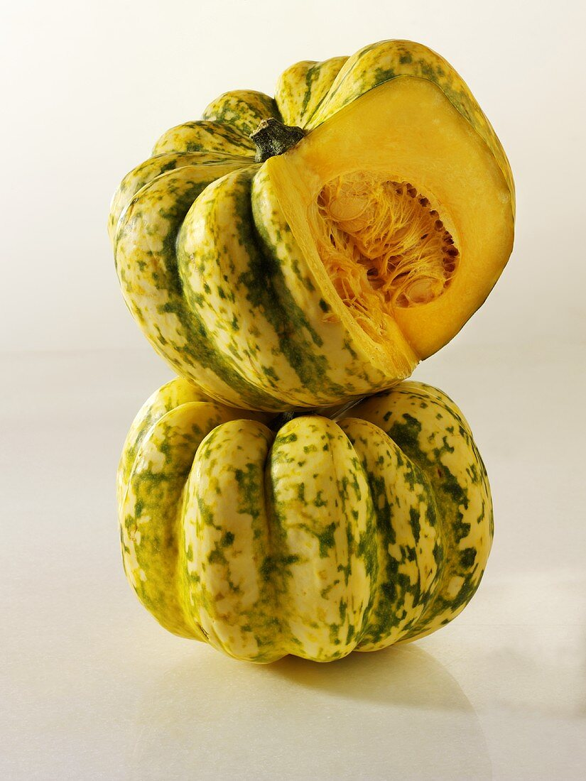 One whole acorn squash & one with a piece cut out, in a pile