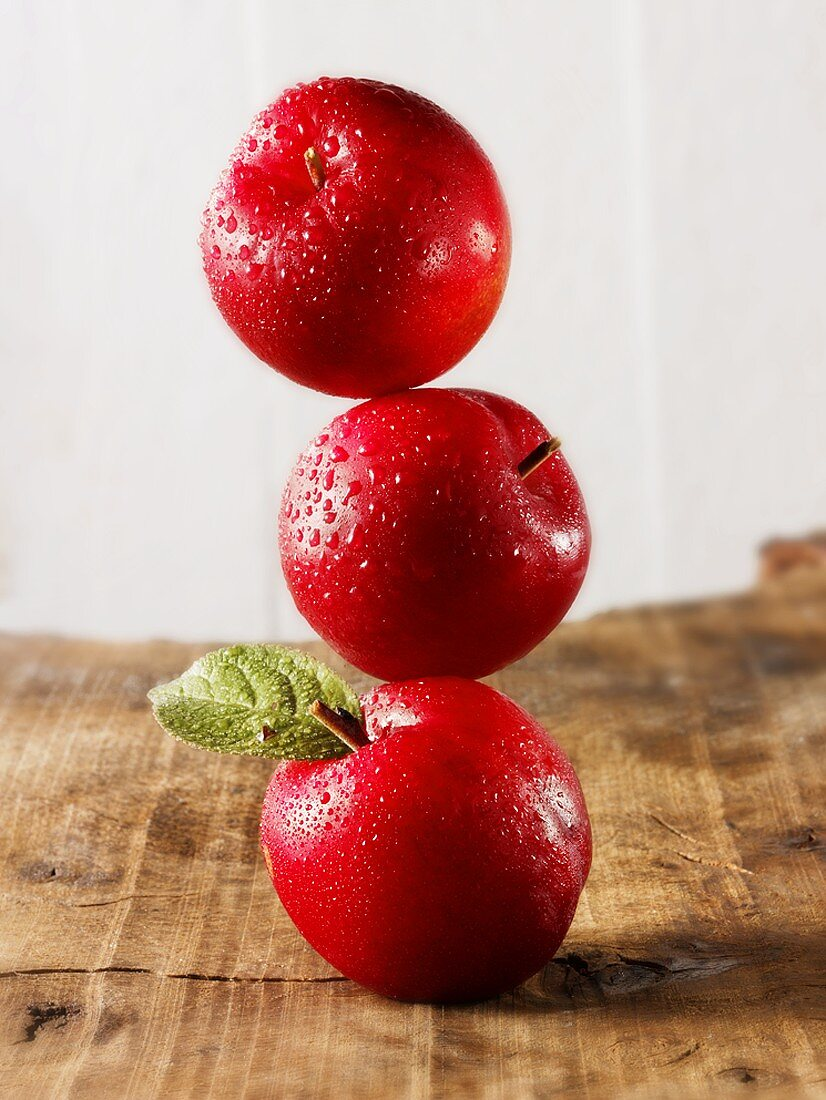 Three red plums, stacked