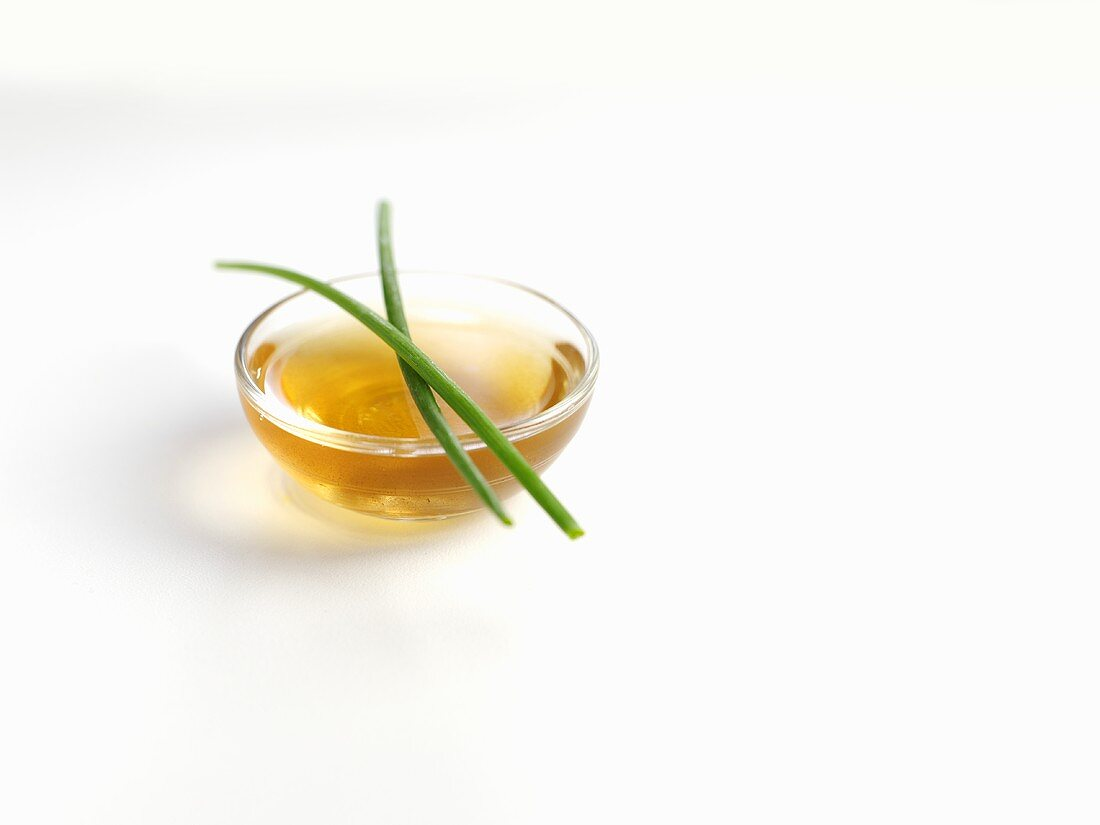Chives on a small glass dish of oil