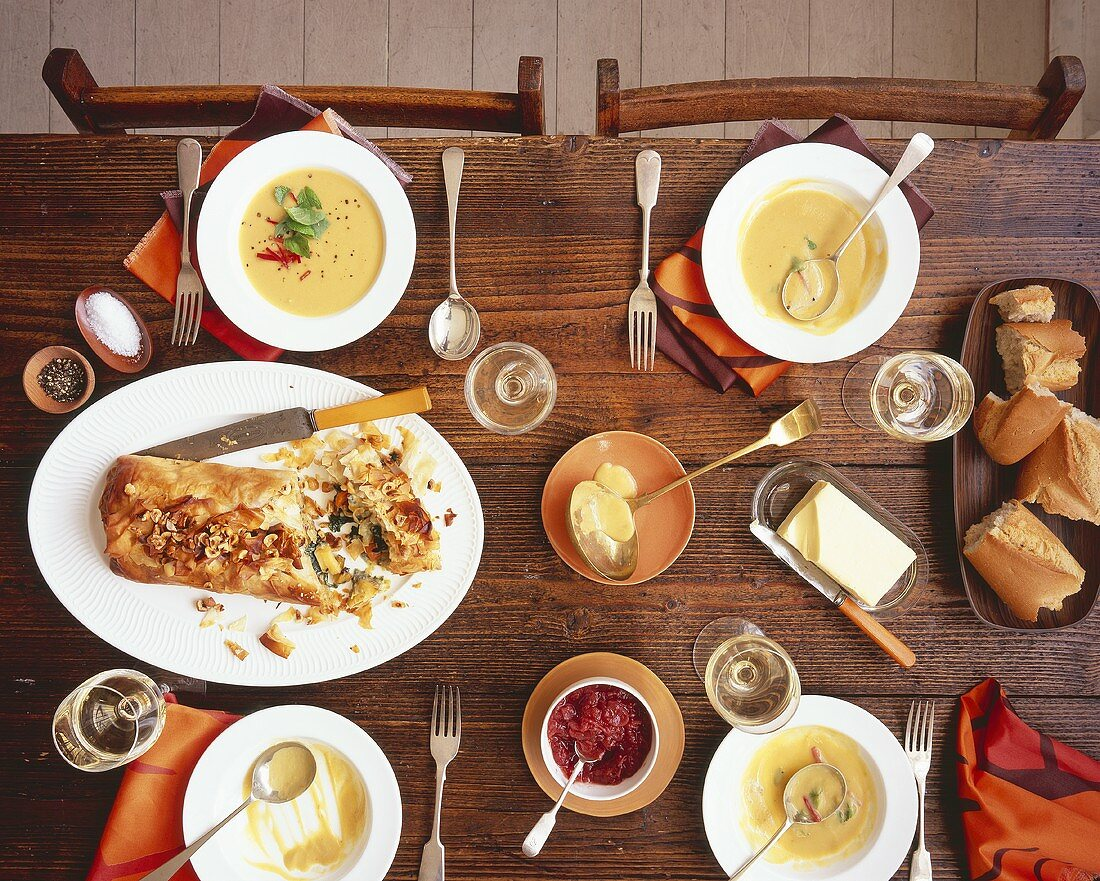 Vegetable strudel and pumpkin coconut soup on laid table
