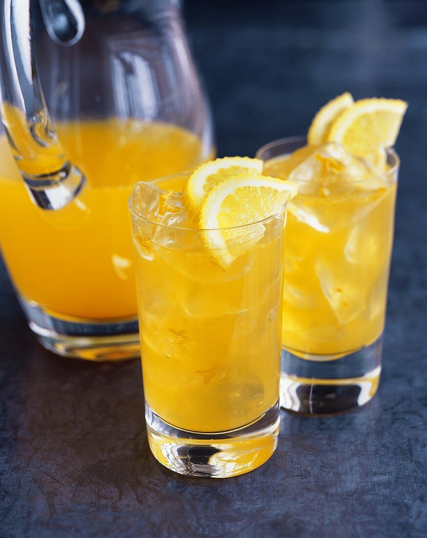 Orangeade in glass jug and two glasses
