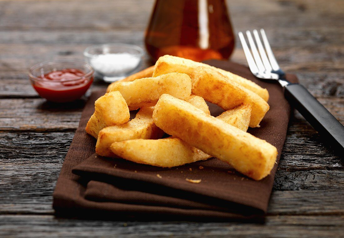 Chips on fabric napkin, salt and ketchup behind