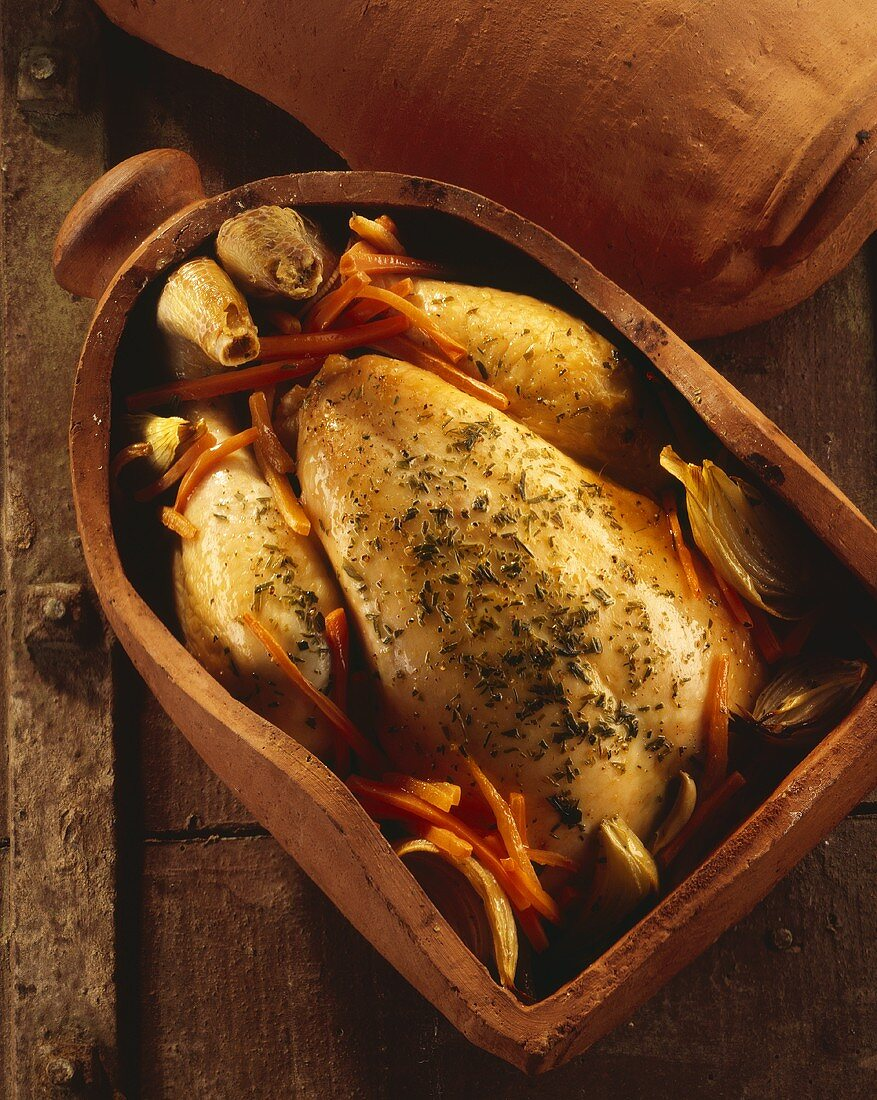 A whole chicken in a clay cooking pot