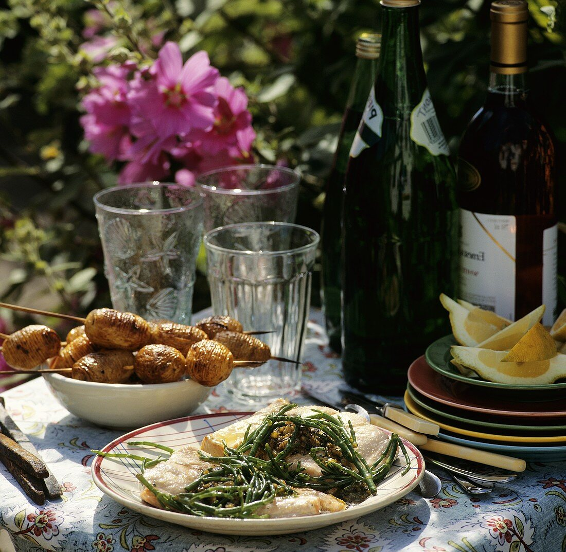 Salmon with glasswort and minced meat kebabs on table in the garden