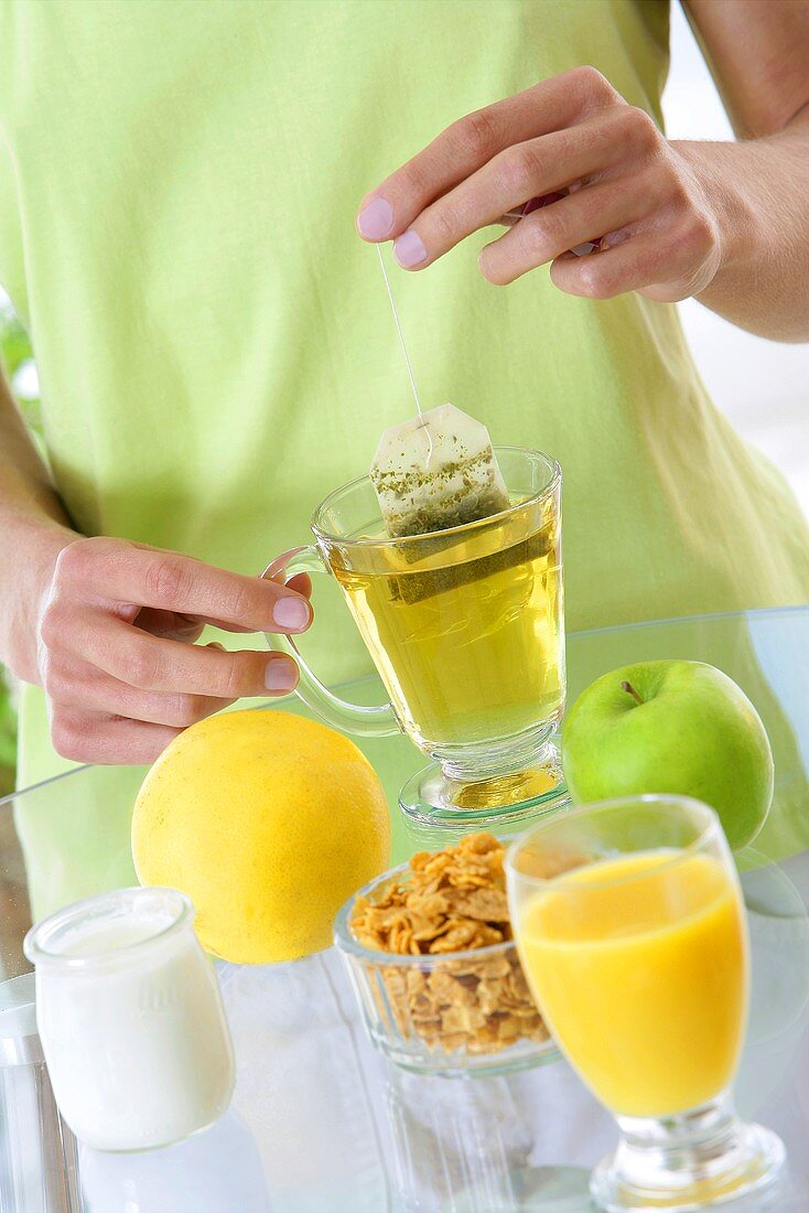 Woman with cup of tea and healthy breakfast