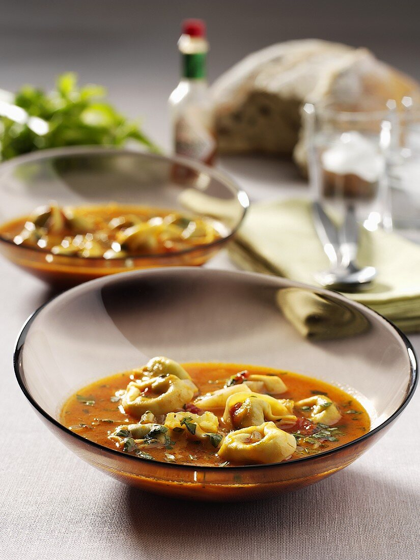 Tortellini soup in two glass dishes