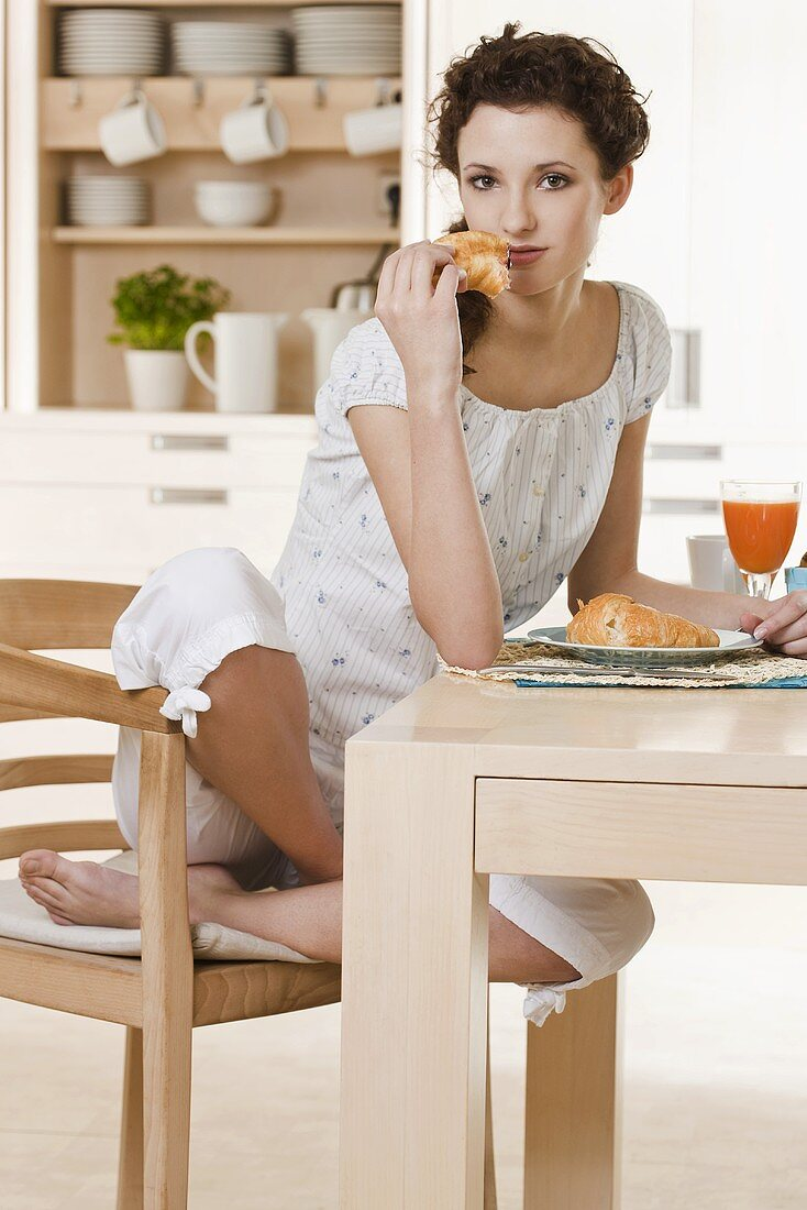 Young woman eating croissant for breakfast