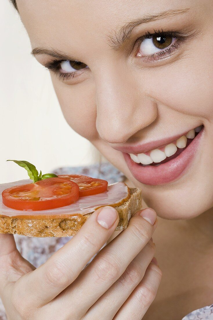 Young woman eating ham & tomato open sandwich (wholemeal)