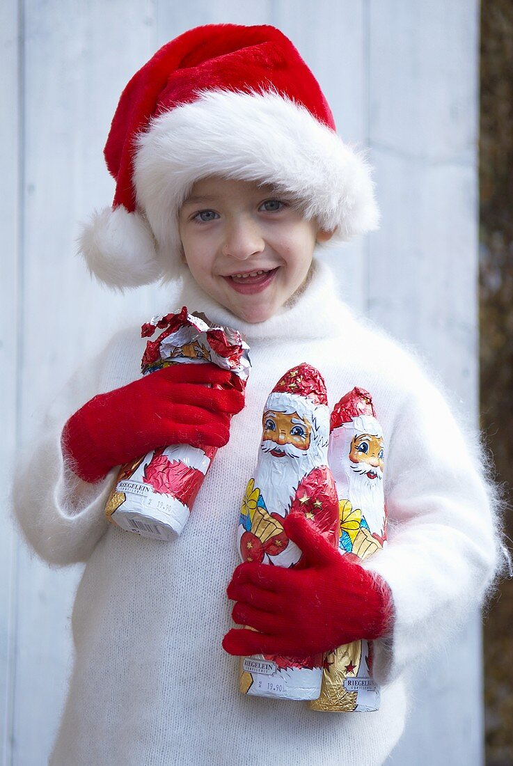 Boy in Father Christmas hat holding chocolate Father Christmases