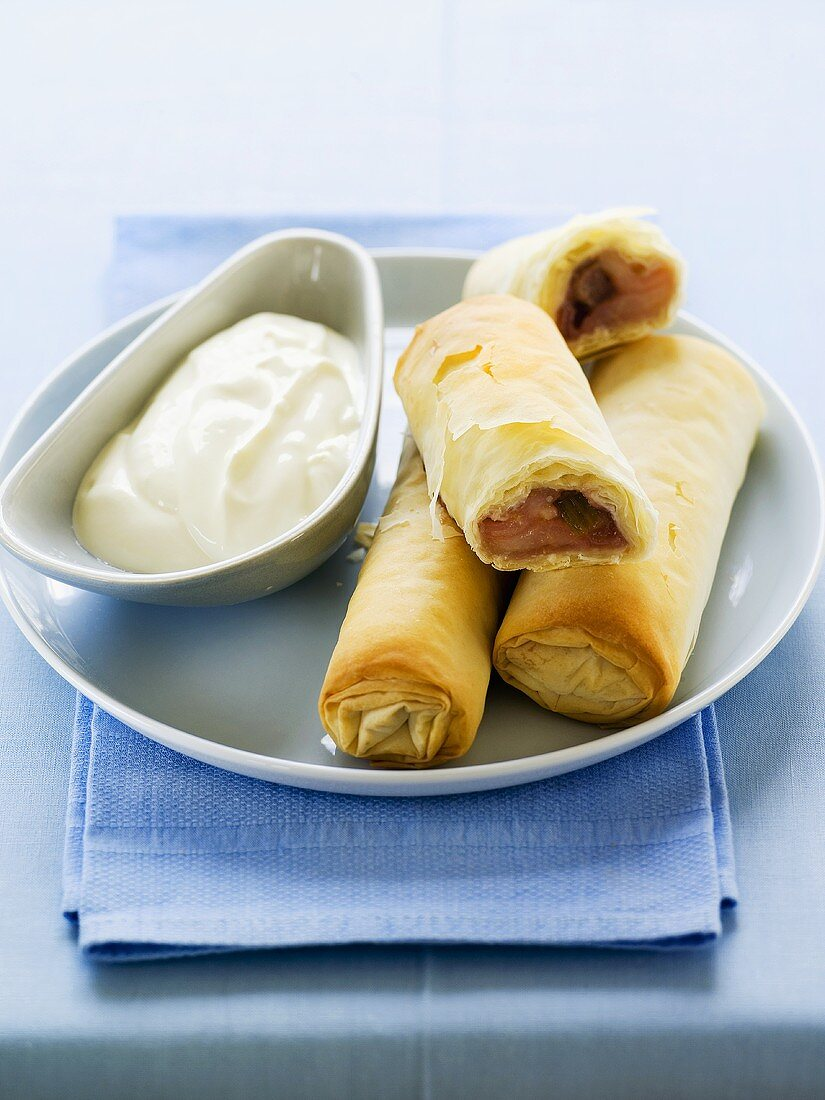 Filo pastry rolls with apple and rhubarb filling and cream