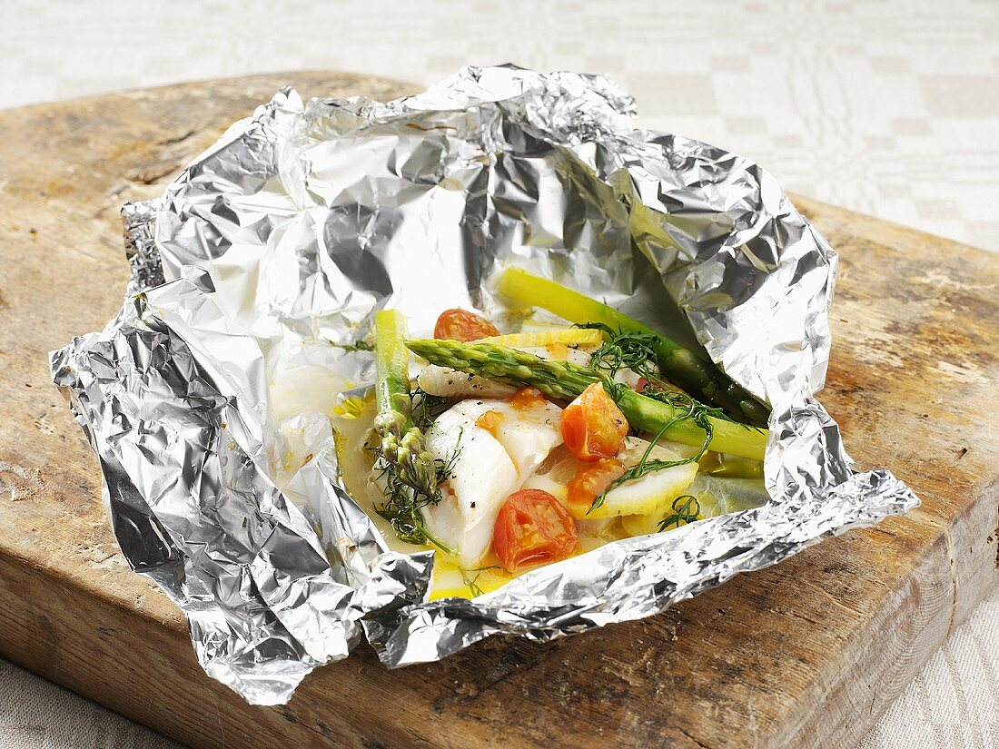 Fish fillet with asparagus and tomatoes in aluminium foil