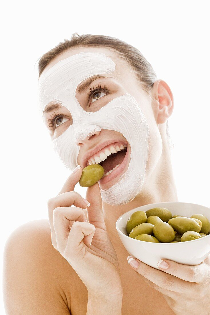 Young woman with facial mask eating green olives