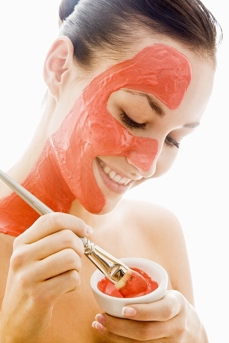 Young woman with red facial mask