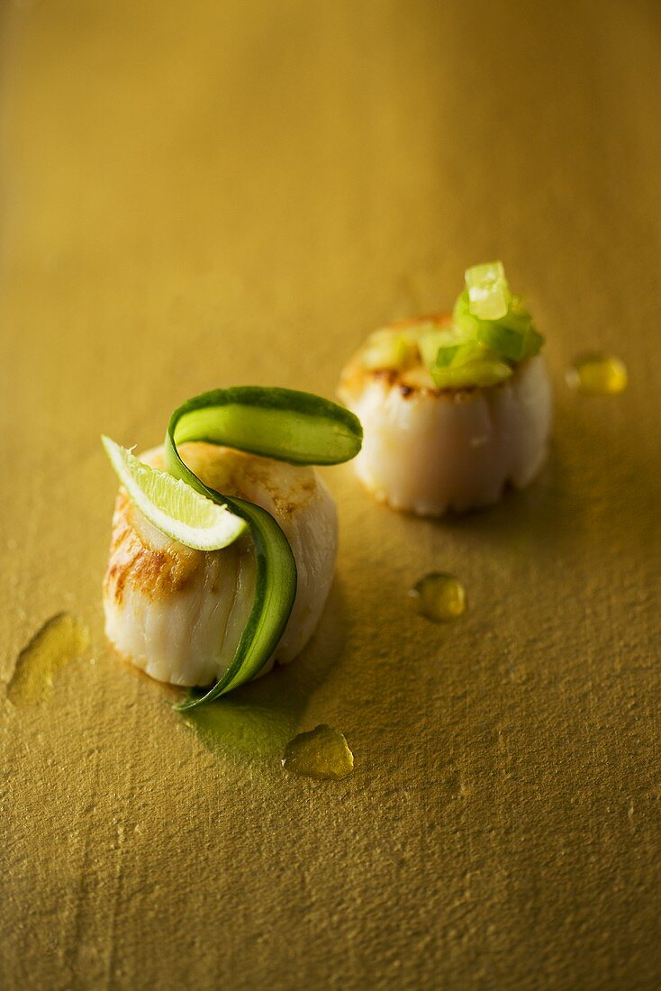 Fried scallops garnished with lime and cucumber