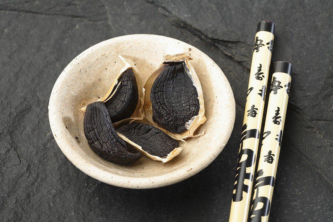 Cloves of black garlic with chopsticks