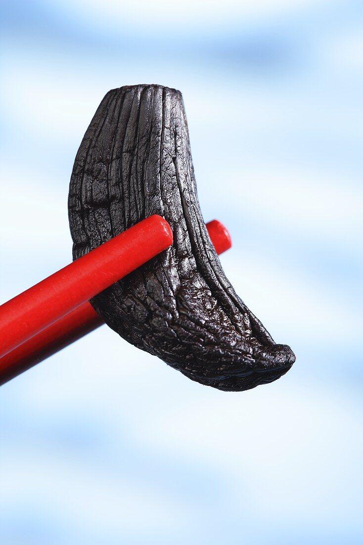 A clove of black garlic between chopsticks
