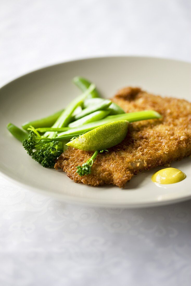 Breaded escalope with broccoli and lime wedge