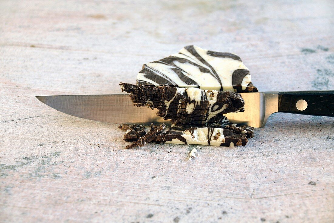 Knife cutting block of marbled chocolate