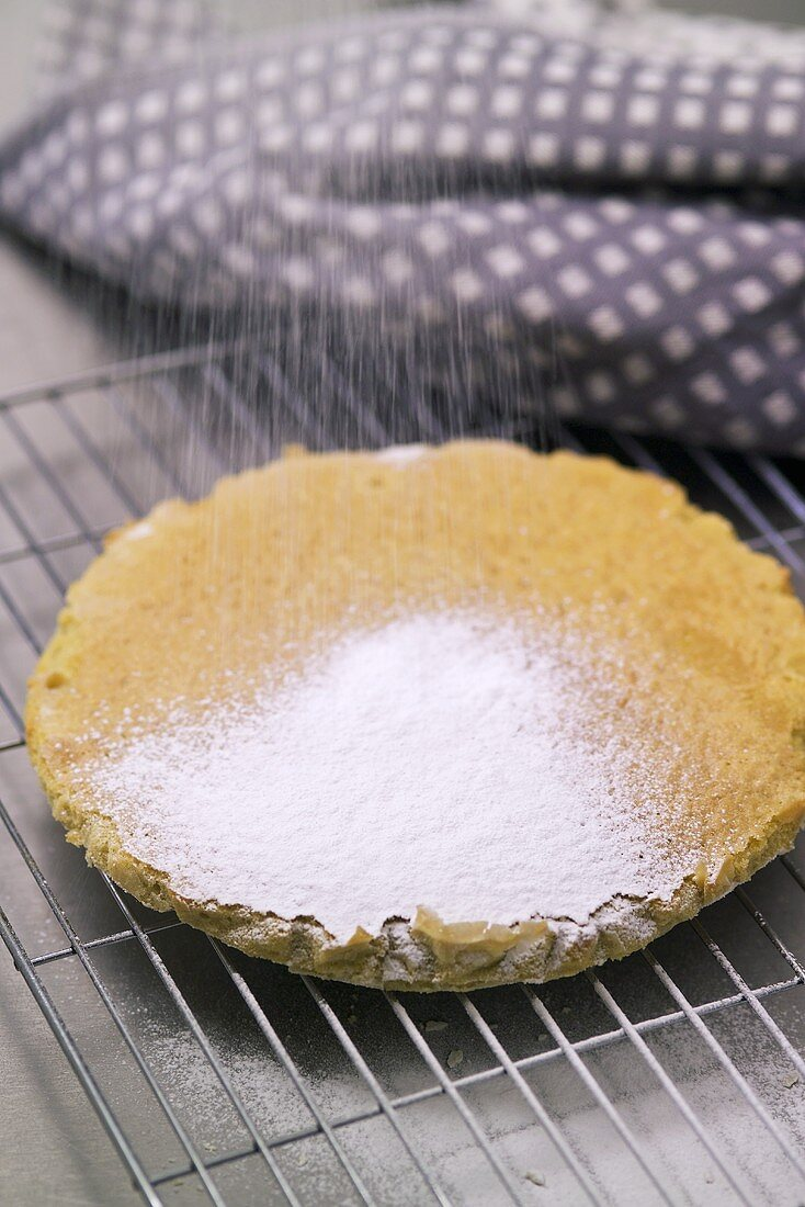 Dusting olive cake with icing sugar
