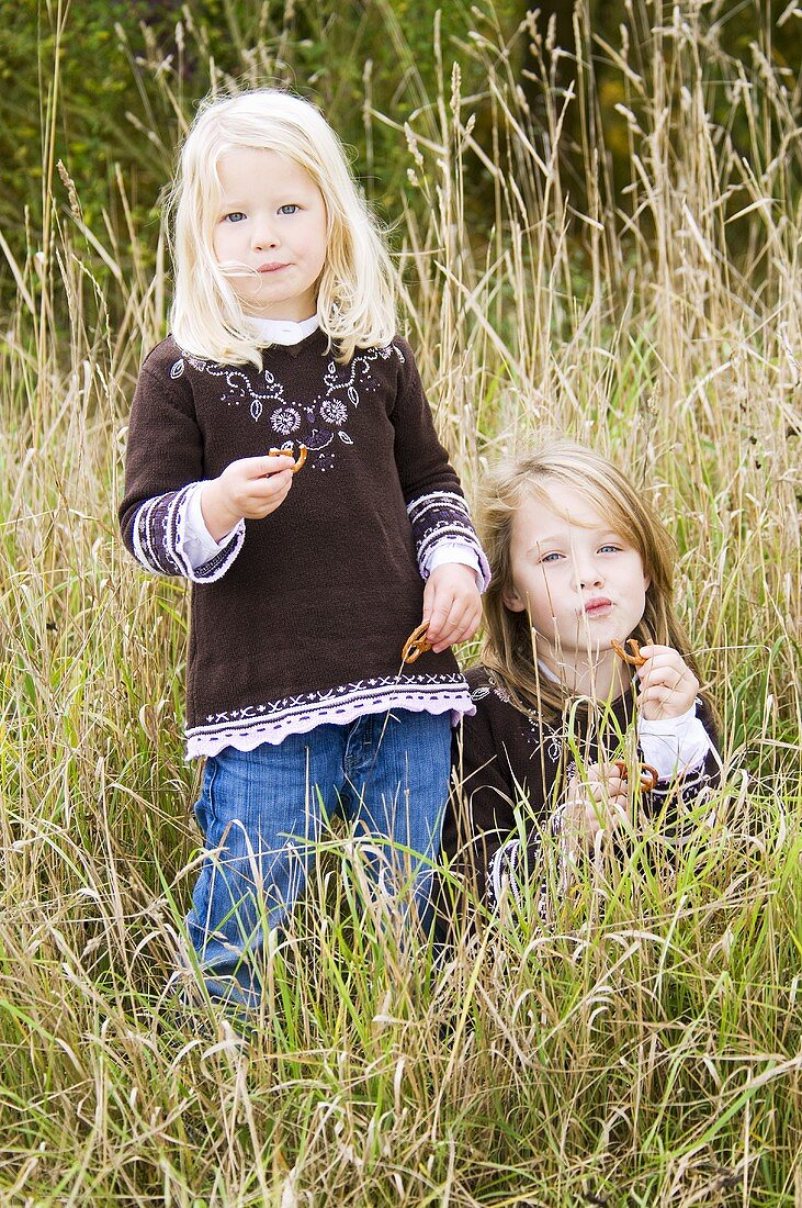Two girls with salted pretzels in long grass