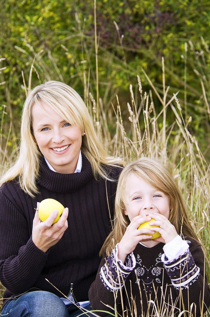 Mother and daughter eating apples in long grass