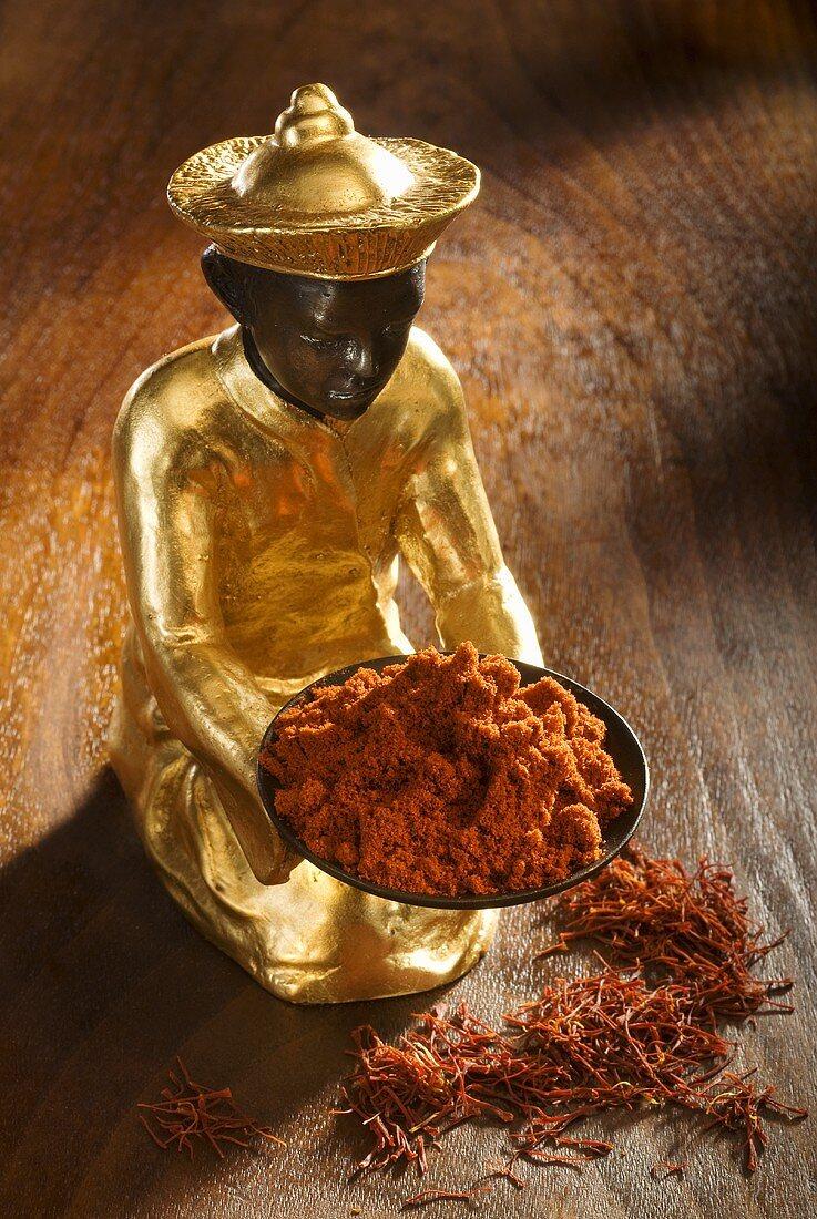Statuette with saffron powder & saffron threads on wooden background