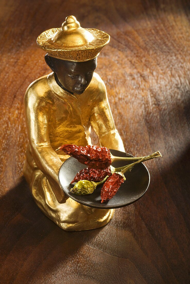 Gilded statuette with dried chillies