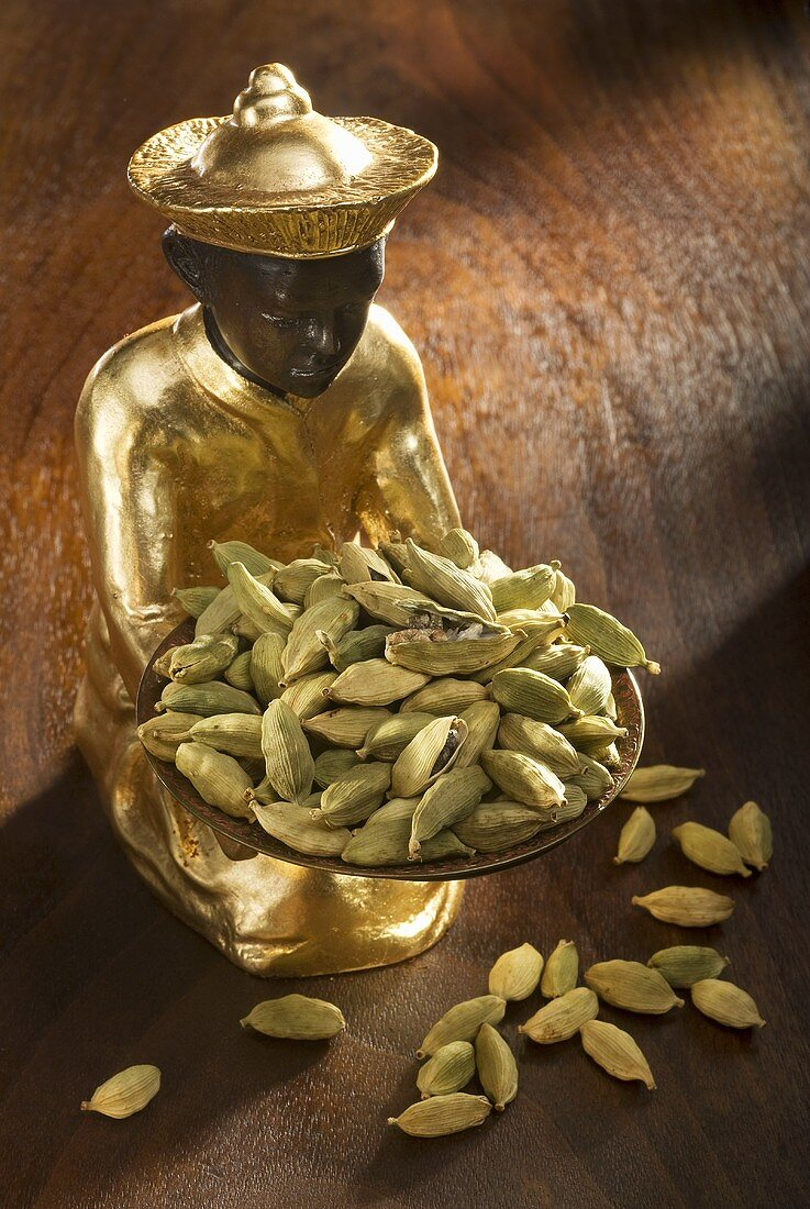 Gilded statuette with cardamom pods