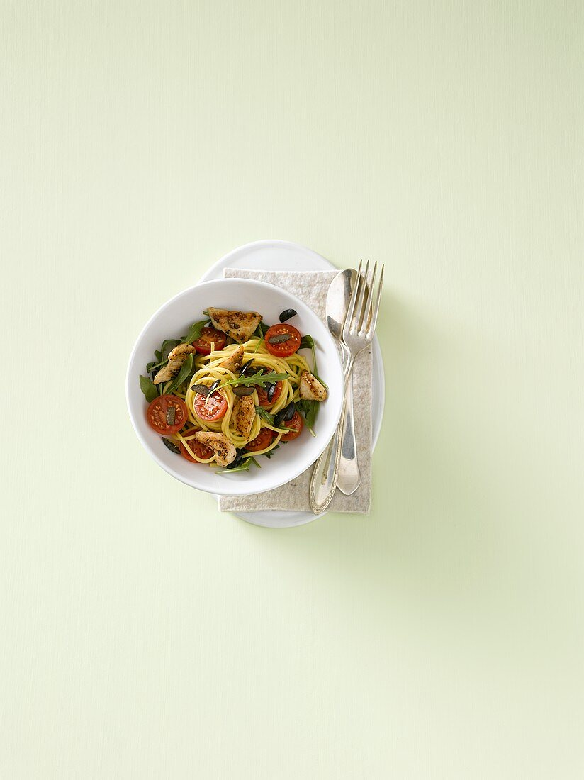 Spaghetti with strips of chicken breast, rocket and tomatoes