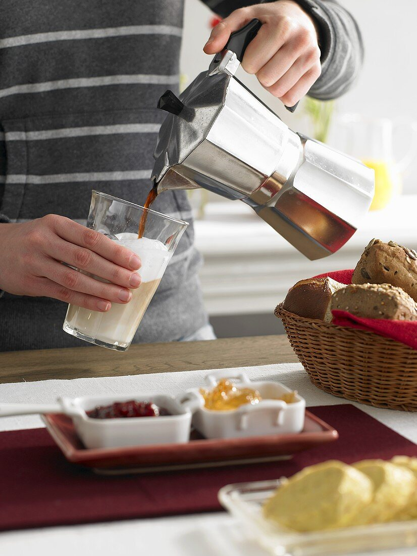 Pouring coffee onto frothed milk