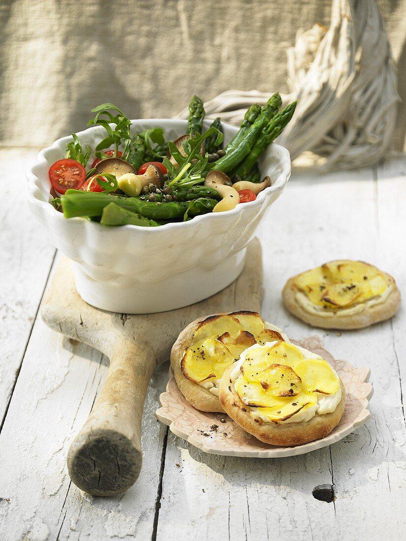 Green asparagus salad with small potato pizzas