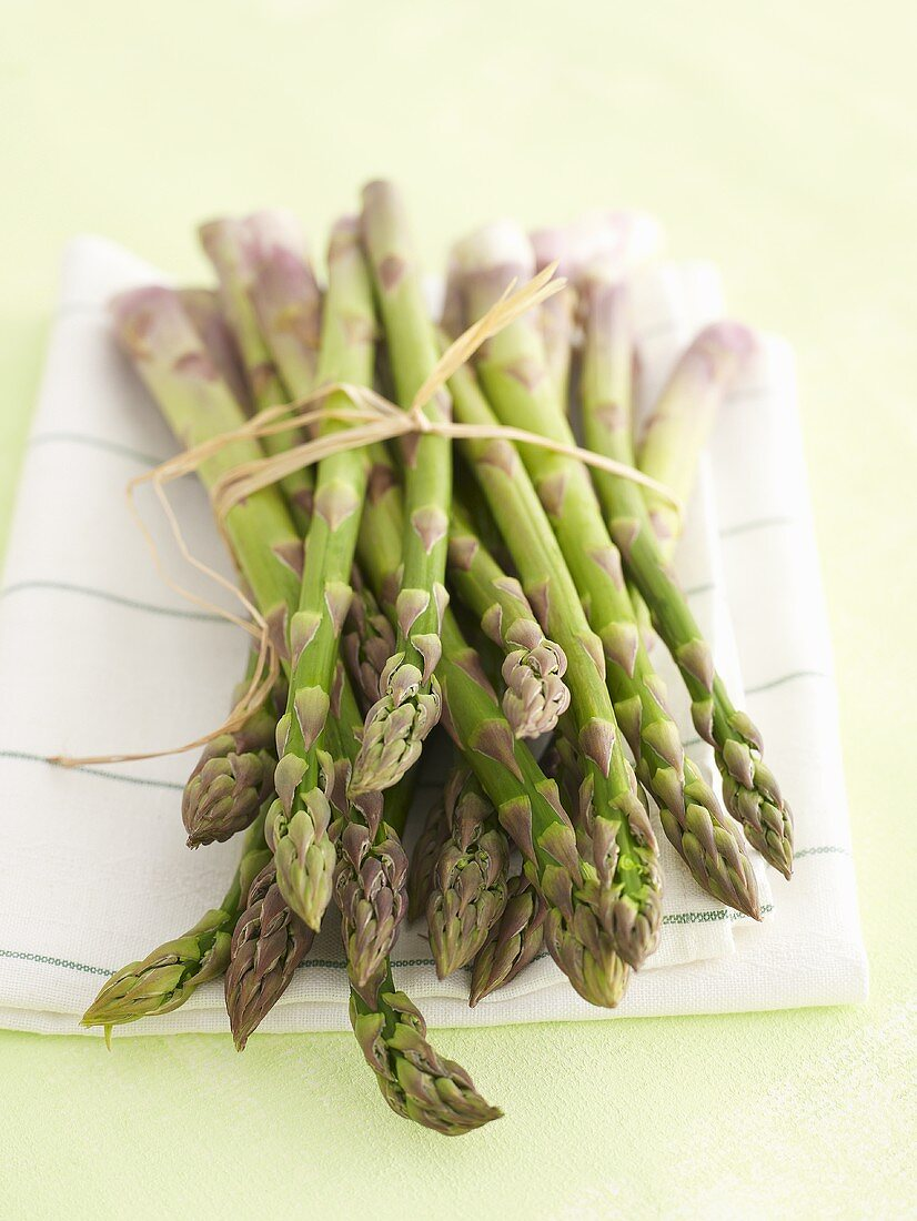 Bundle of green asparagus on tea towel